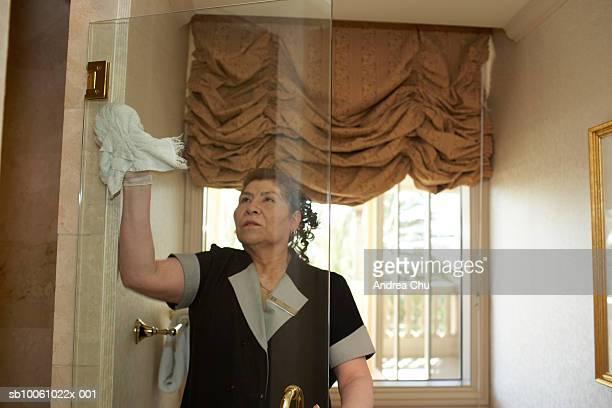 maid clearing glass door in hotel bathroom - メイド ストックフォトと画像