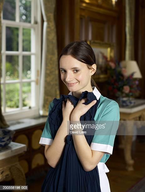 Maid holding suit, smiling, portrait
