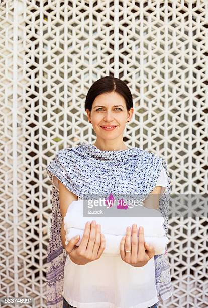 maid holding white towels in tropical hotel - izusek stock pictures, royalty-free photos & images