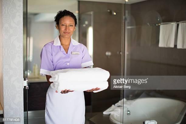 Maid in doorway of bathroom