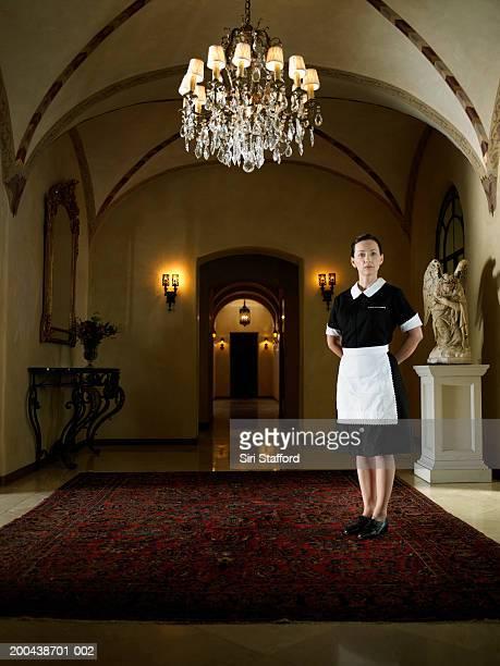 maid in uniform standing in hallway - メイド ストックフォトと画像