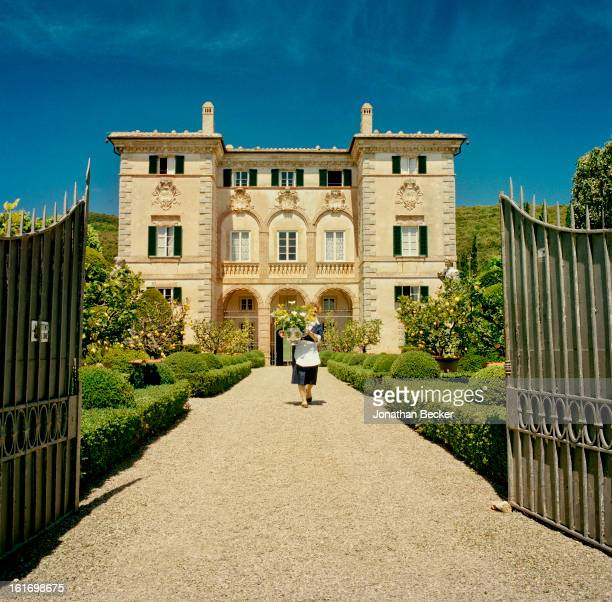 A maid is photographed for Vanity Fair Magazine on May 11 2012 transporting flowers arrangements through the gardens of Villa Cetinale in Siena Italy...