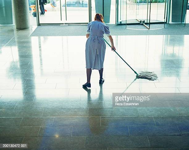 Maid mopping hotel lobby floor