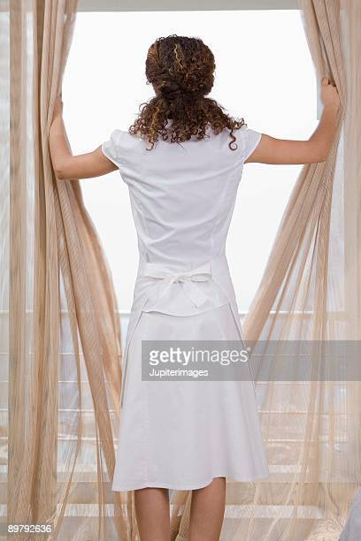 Maid opening curtains in hotel room