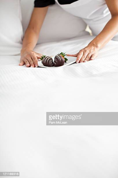Maid placing plate of strawberries on bed