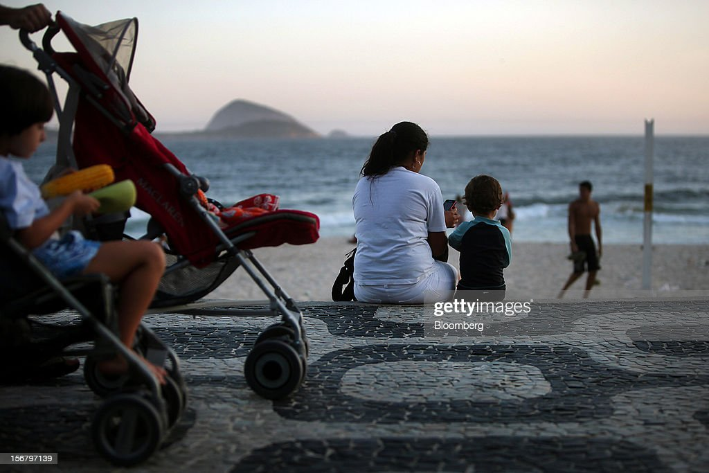 A maid sits with a child at the Baixo Bebe beach playground in Rio de Janeiro, Brazil, on Monday, Nov. 19, 2012. With unemployment in Latin America's biggest economy at record lows, poor women who for decades formed a pool of cheap domestic labor for the middle and upper classes are pursuing better-paying, higher-skilled jobs. Photographer: Dado Galdieri/Bloomberg via Getty Images