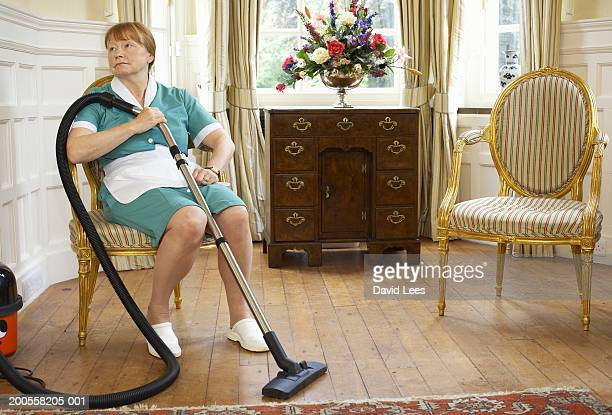 Maid sitting on chair holding vacuum cleaner