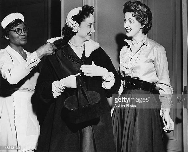 A maid takes the coat of American journalist and television game show panelist Dorothy Kilgallen circa 1950