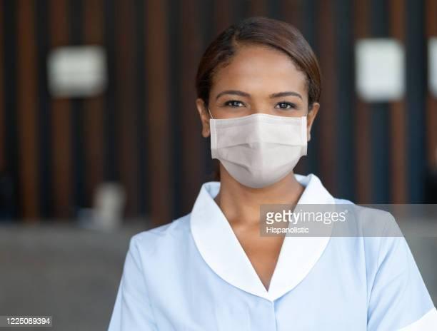 ホテルで働いている間コロナウイルスの拡散を避けるためにフェイスマスクを着用したメイド - メイド ストックフォトと画像