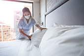 Maid working at a hotel and doing the bed wearing a facemask