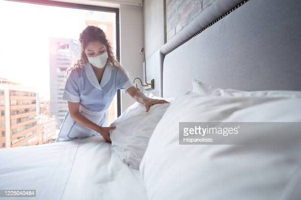 maid working at a hotel and doing the bed wearing a facemask - hotel stock pictures, royalty-free photos & images