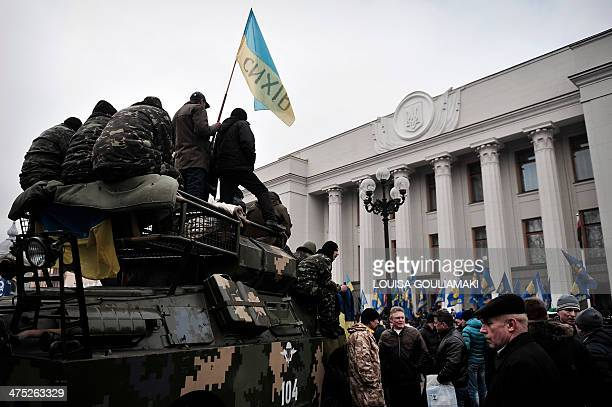 Maidan self defence activists guard atop an armoured vehicle in front of the parliament in Kiev on February 27 2014 Deposed Ukrainian president...