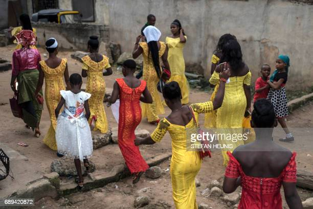Maidens of honour walk to receive the bride Chinyere at the Mount of Holiness Church in the Osusu district Aba on May 28 2017 The Nigerian civil wars...