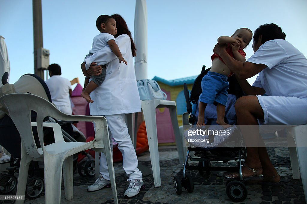Maids hold childred at the Baixo Bebe beach playground in Rio de Janeiro, Brazil, on Monday, Nov. 19, 2012. With unemployment in Latin America's biggest economy at record lows, poor women who for decades formed a pool of cheap domestic labor for the middle and upper classes are pursuing better-paying, higher-skilled jobs. Photographer: Dado Galdieri/Bloomberg via Getty Images
