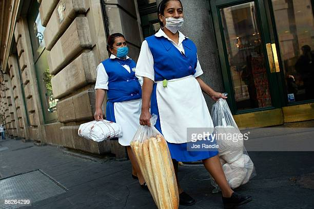Maids wear surgical masks to help prevent being infected with the swine flu as they walk through the street on April 28 2009 in Mexico City Mexico...