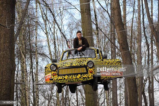 Maik Dannewitzsch poses in a Trabant car he fixed on March 20 2012 in the high ropes course of the adventure park Moritzburg near Dresden eastern...