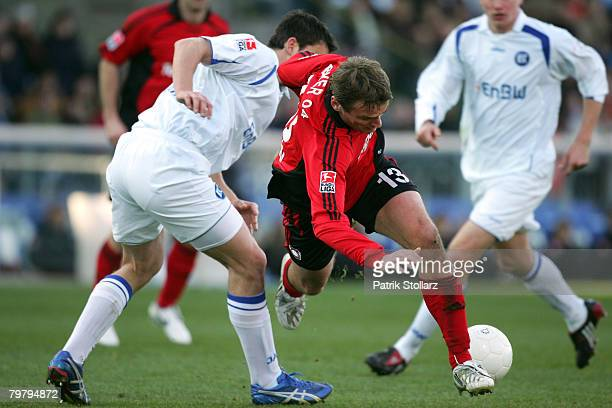 Maik Franz of Karlsruhe competes with Dmitry Bulykin of Leverkusen during the Bundesliga match between Karlsruher SC andBayer Leverkusen at the...