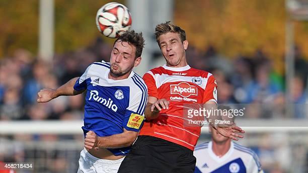Maik Kegel of Kiel and Tom Schuetz of Bielefeld head for the ball during the Third League match between Holstein Kiel and Arminia Bielefeld at...