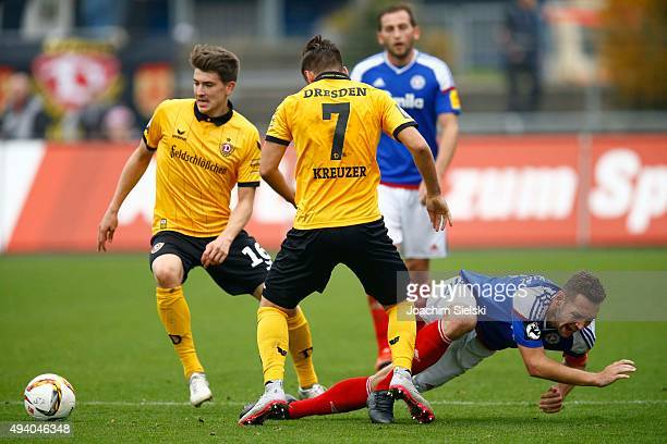 Maik Kegel of Kiel challenges JimPatrick Mueller and Niklas Kreuzer of Dresden during the Third League match between Holstein Kiel and Dynamo Dresden...