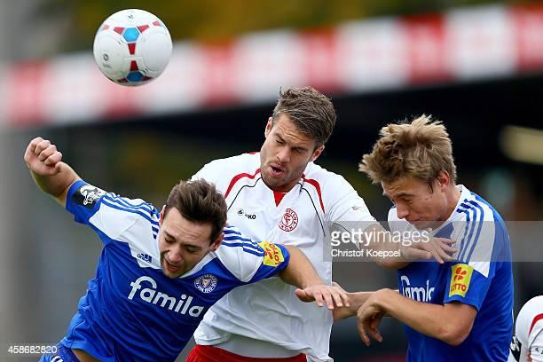 Maik Kegel of Kiel Florian Hoernig of Fortuna Koeln and Hauke Wahl of Kiel go up for a header during the third League match between Fortuna Koeln and...