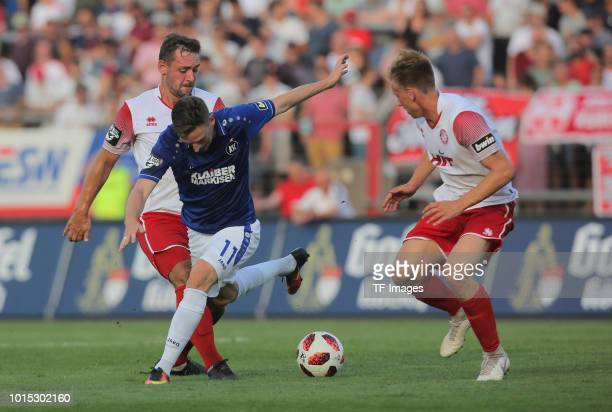 Maik Kegel of Koeln Martin Roeser of Karlsruher SC and Nico Brandenburger of Koeln battle for the ball during the 3 Liga match between SC Fortuna...