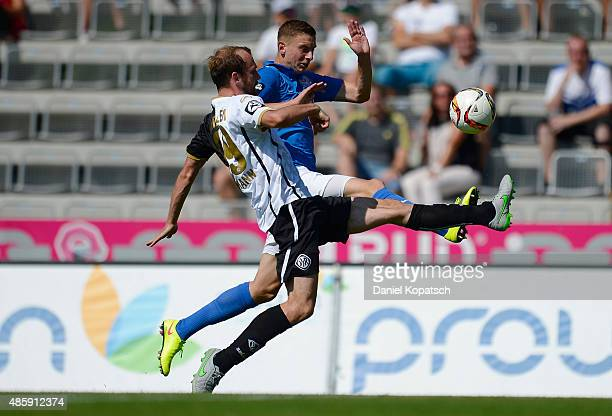 Maik Lukowicz of Rostock is challenged by Sebastian Neumann of Aalen during the third league match between VfR Aalen and Hansa Rostock at ScholzArena...