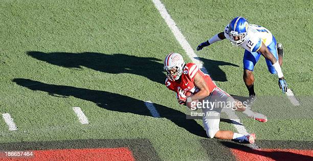 Maika Mataele of the UNLV Rebels catches a pass as Forrest Hightower of the San Jose State Spartans defends during the fourth quarter of their game...