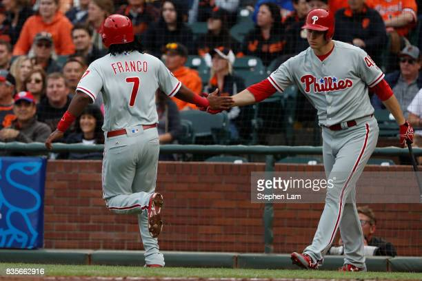 Maikel Franco is congratulated by teammate Jerad Eickhoff after scoring on a sacrifice fly by Cameron Perkins during the second inning against the...