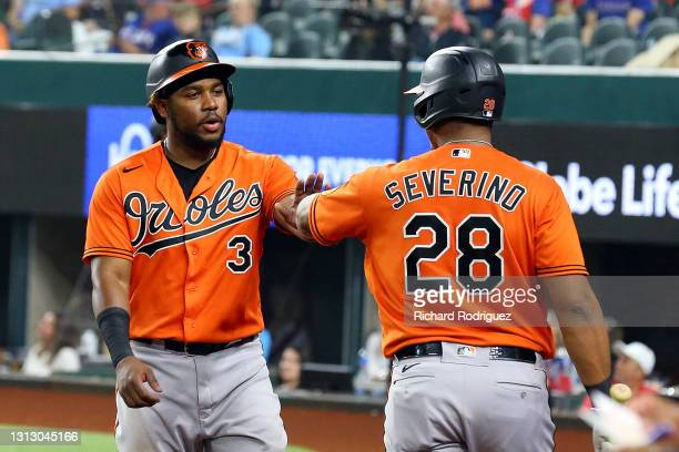 Maikel Franco of the Baltimore Orioles is greeted at the dugout by Pedro Severino of the Baltimore Orioles after scoring on a sacrifice fly in the...
