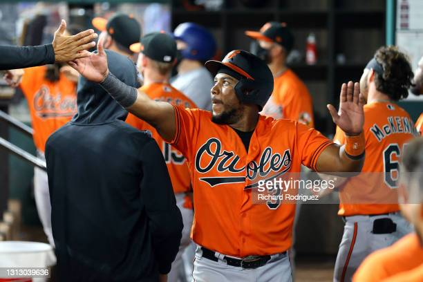 Maikel Franco of the Baltimore Orioles is greeted in the dugout after scoring on a sacrifice fly in the eighth inning of the MLB game against the...