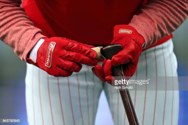 Maikel Franco of the Philadelphia Phillies applies pine tar and wears Franklin batting gloves as he prepares his bat before a game against the Miami...