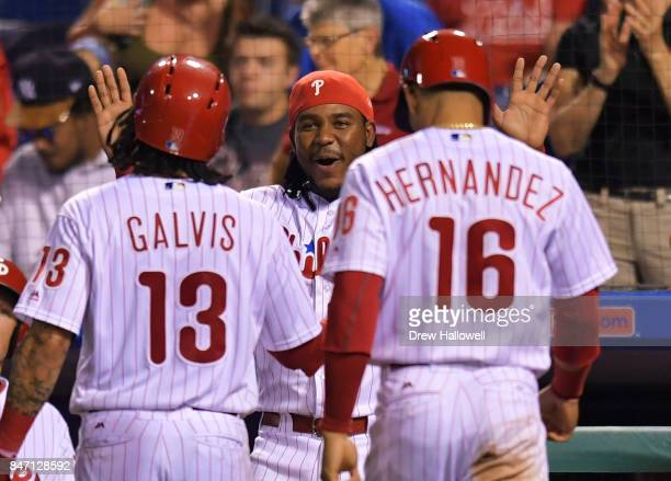 Maikel Franco of the Philadelphia Phillies congratulates Freddy Galvis and Cesar Hernandez after they scored in the second inning against the Miami...