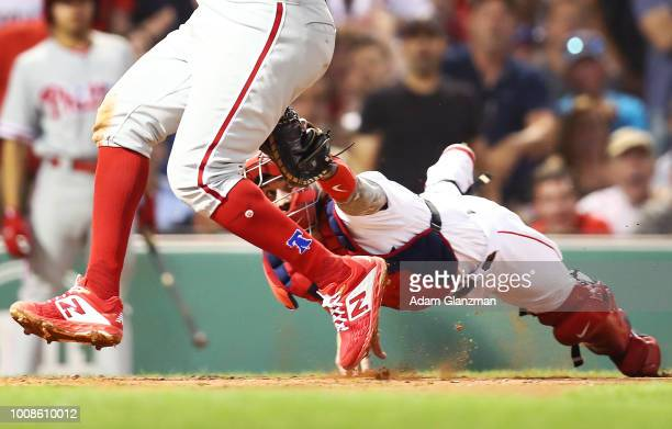 Maikel Franco of the Philadelphia Phillies evades the tag at home plate by Blake Swihart of the Boston Red Sox to score in the fourth inning of a...