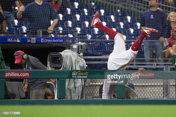 Maikel Franco of the Philadelphia Phillies falls over the camera fence reaching for a foul ball in the top of the eighth inning against the...