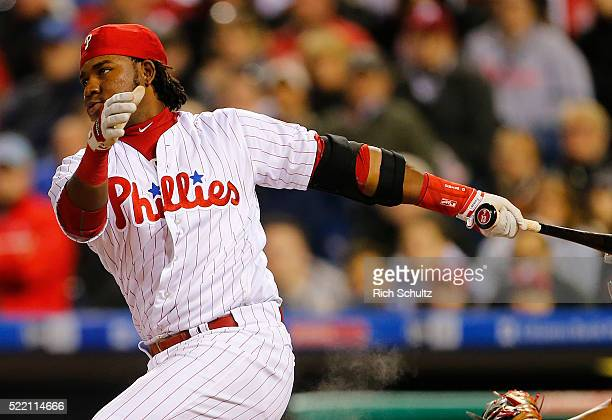 Maikel Franco of the Philadelphia Phillies swings and misses as his helmet flies off his head during the third inning against the Washington...