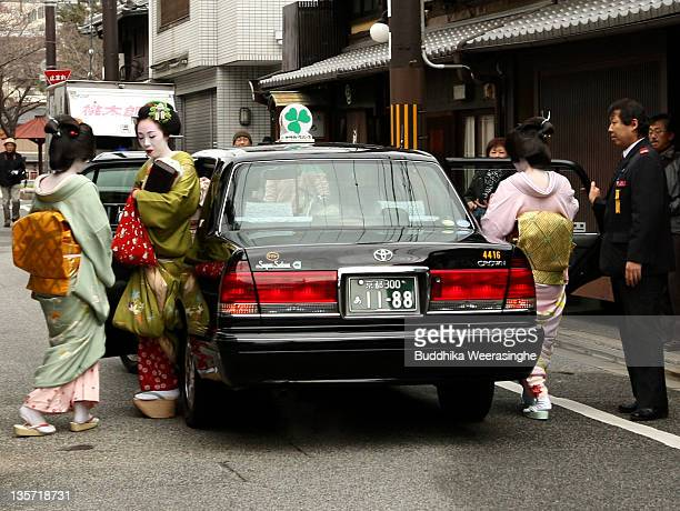 Maiko and geiko geisha girls get in to the taxi after bowing to their teacher of traditional art and tea houses to show their gratitude for the past...