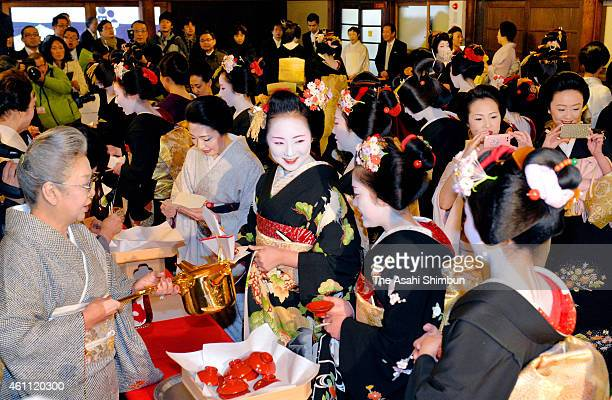 Maiko and geiko in black formal kimonos are offered the 'omiki' sacred sake during a ceremony to mark the start of business in the New Year at Gion...