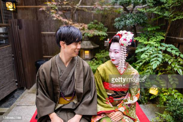 'maiko' (geisha in training) and young man in hakama sitting and looking each other in small japanese garden - three quarter length stock pictures, royalty-free photos & images