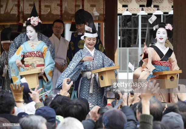 Maiko apprentice geisha scatter roasted beans packed in small bags to drive away demons at Yasaka Shrine in the former capital of Kyoto on Feb 2 as...