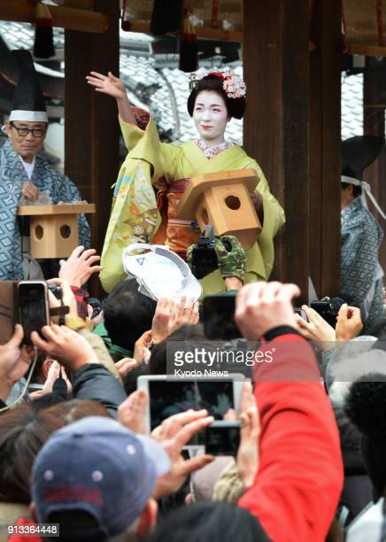 A maiko apprentice geisha scatters roasted beans to drive away demons during the annual Setsubun ceremony at Yasaka Shrine in Kyoto on Feb 2 2018...