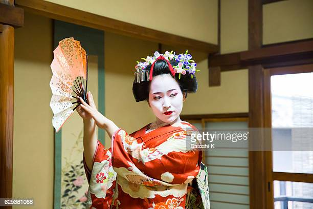 maiko girl dancing with paper fan in japanese tatami room - geisha fotografías e imágenes de stock
