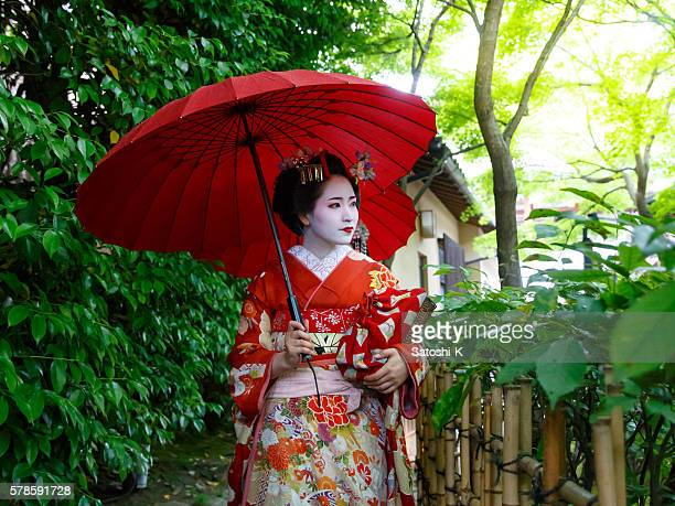 Maiko girls walking through narrow path in green leaves