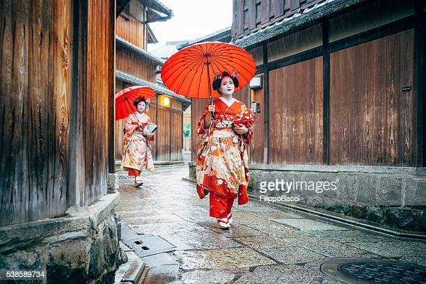 maiko women walking in kyoto - kyoto prefecture stock pictures, royalty-free photos & images