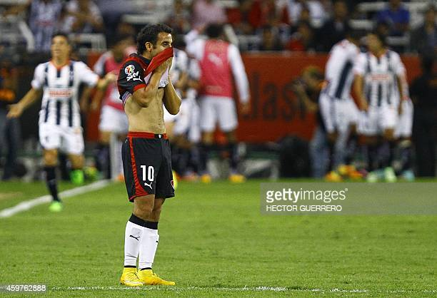 Maikon Souza of Atlas reacts as Monterrey players celebrate their score during a quarterfinal football match of 2014 Mexican Apertura tournament...