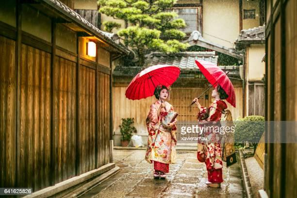 Maikos holding red umbrellas during rainy season