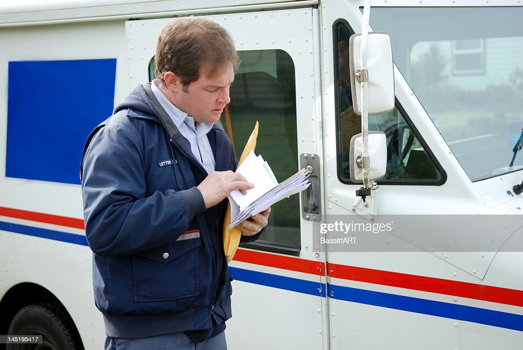 Mail carrier sorting mail near delivery truck : Stock Photo