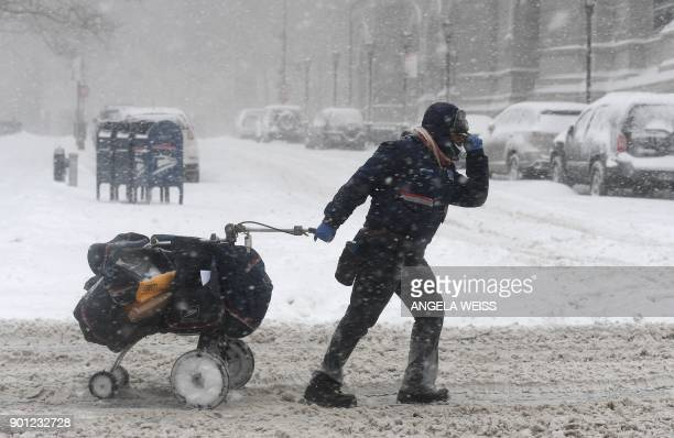 TOPSHOT A mail delivery person pulls her cart through the snow on January 4 2018 in Brooklyn New York A giant winter bomb cyclone walloped the US...