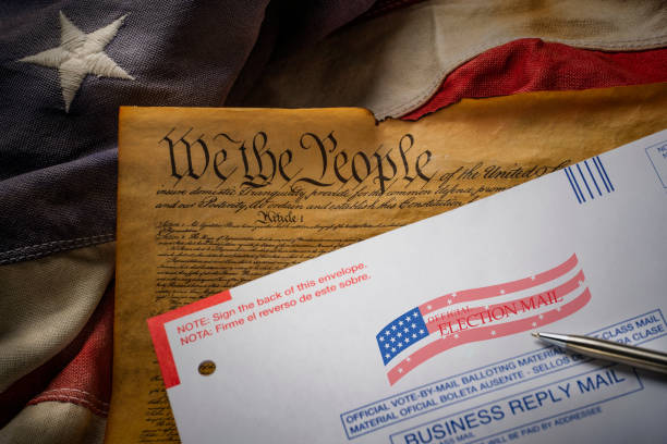 2020 mail in election envelope resting on the Constitution and American flag.