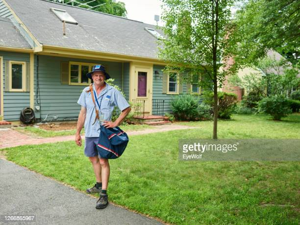 a mail man walking away from a house with a mail sack hanging off his shoulder, looking into camera smiling. - postal worker stock pictures, royalty-free photos & images