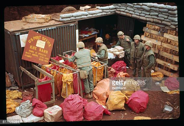 Mail packaged in colorful sacks is unloaded from a truck at the post office set up in a sandbagged bunker